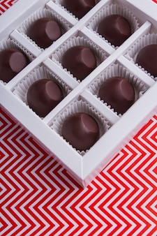 Caramelle di cioccolato rotonde del primo piano nella scatola quadrata