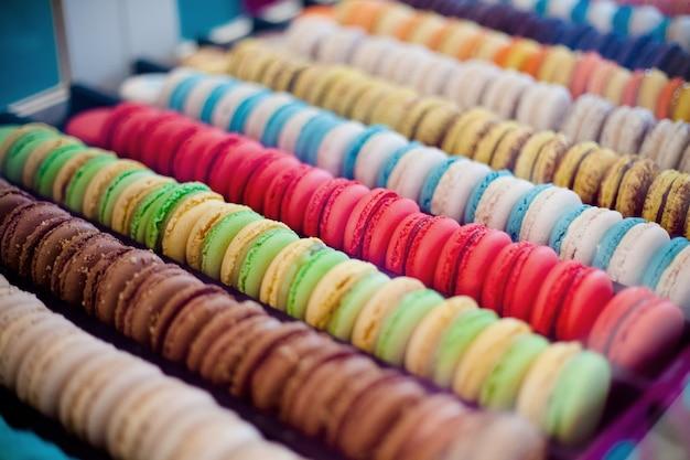 Primo piano di righe e colonne di macarons multicolori, biscotti francesi tradizionali.