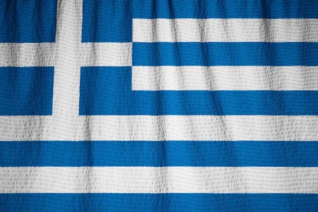 Primo piano della bandiera increspata della grecia, bandiera della grecia che soffia in vento