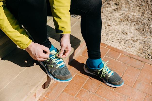 Primo piano dell'uomo del corridore che lega i lacci delle scarpe su scarpe da ginnastica che si siedono sulle scale al mattino