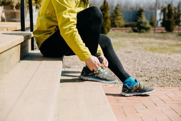 Primo piano dell'uomo del corridore che lega i lacci delle scarpe su scarpe da ginnastica che si siedono sulle scale di legno