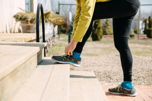 Primo piano dell'uomo del corridore che lega i lacci delle scarpe su scarpe da ginnastica sulle scale di legno che si prepara a correre