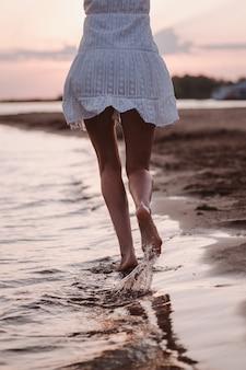 Primo piano di una foto di una donna che corre con le gambe vista posteriore di una bella donna abbronzata in un abito estivo bianco...