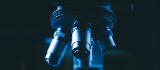 Primo piano del microscopio scientifico con la lente del metallo in laboratorio, attrezzatura di laboratorio - microscopio ottico.
