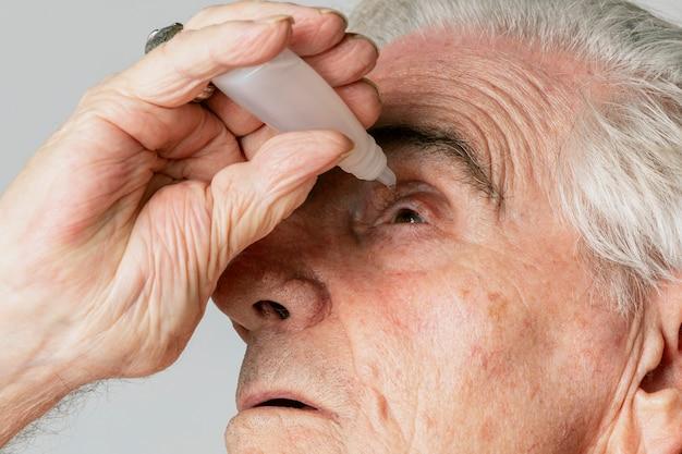 Uomo anziano del primo piano che applica collirio