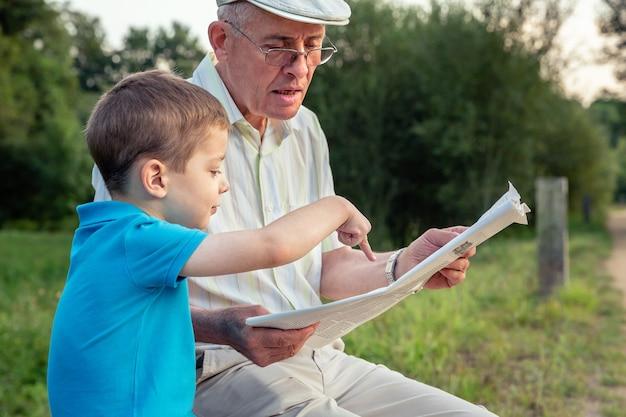 Primo piano dell'uomo anziano che legge il giornale e del bambino carino che punta un articolo con il dito su uno sfondo naturale. due diverse generazioni concetto.