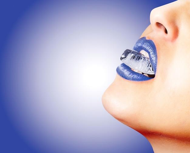 Primo piano delle labbra sensuali con rossetto blu e un cubetto di ghiaccio