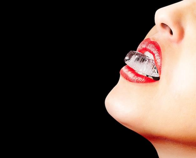 Primo piano delle labbra sensuali con rossetto rosso e un cubetto di ghiaccio