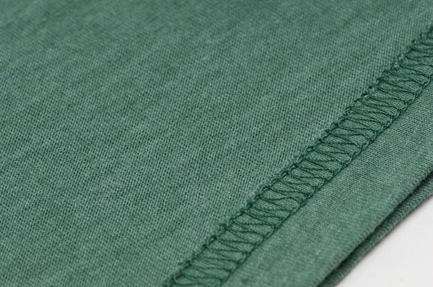 Primo piano di cucire la cucitura su tessuto verde