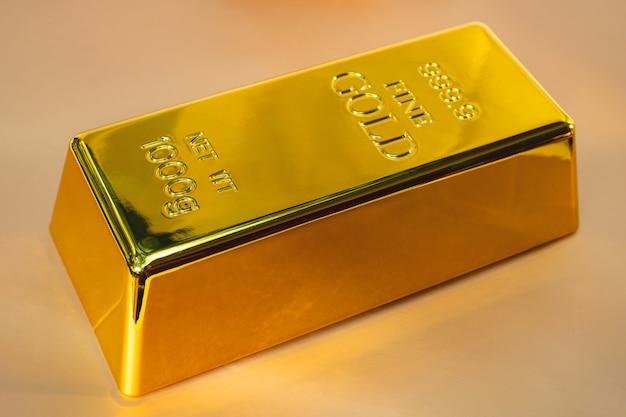 Primo piano lucido un lingotto d'oro 1 kg su sfondo giallo