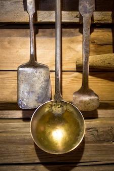 Colpo del primo piano dell'utensile antico del metallo che appende sulla parete di legno