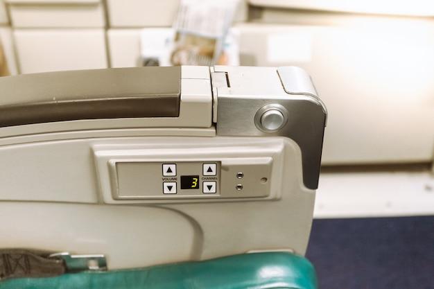 Primo piano del bracciolo sul sedile dell'aereo con pulsanti