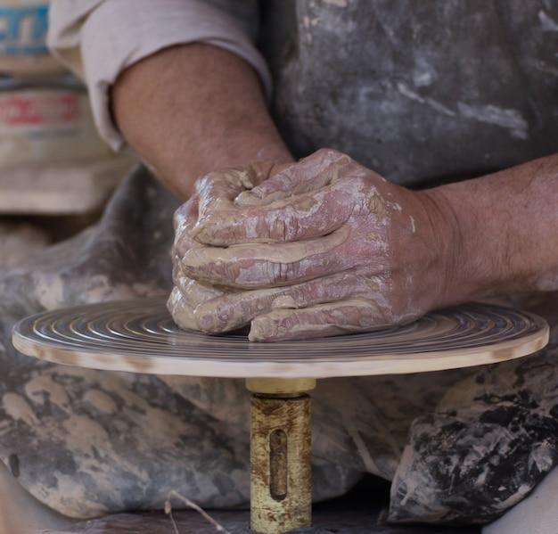 Colpo del primo piano delle mani dei vasai dell'artigiano che scolpiscono il vaso
