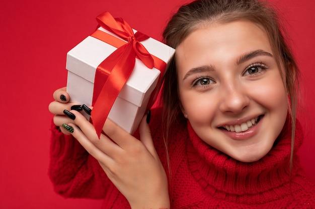 Primo piano di una giovane donna bruna sorridente positiva attraente isolata su una parete di sfondo colorata che indossa abiti alla moda di tutti i giorni con una scatola regalo e guardando di lato