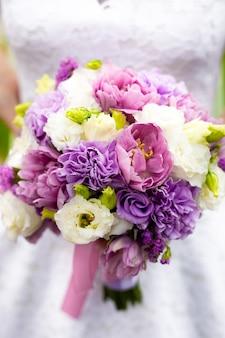 Primo piano di una bellissima sposa che tiene in mano un bouquet da sposa con fiori bianchi, rosa e viola