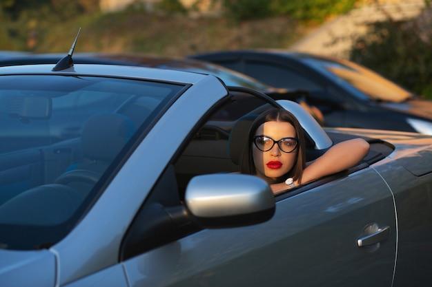 Colpo del primo piano di bella donna castana con le labbra rosse con gli occhiali alla guida di una cabriolet. spazio per il testo