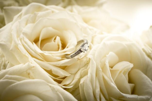 Primo piano di un bellissimo anello di fidanzamento con diamante sdraiato su una rosa bianca