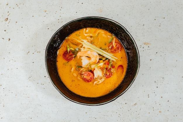 Colpo del primo piano di una ciotola di zuppa deliziosa di tom yum su un tavolo bianco