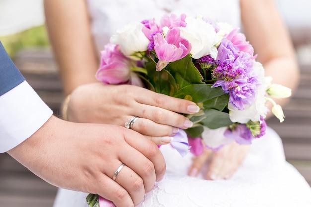 Primo piano della sposa e dello sposo che tengono un bellissimo bouquet da sposa