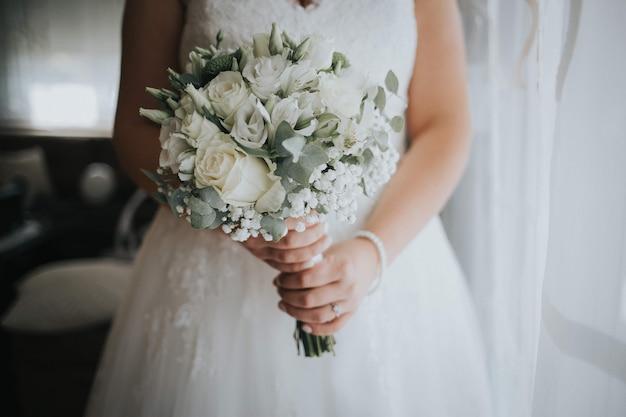 Colpo del primo piano di una sposa che tiene un bel mazzo Foto Premium