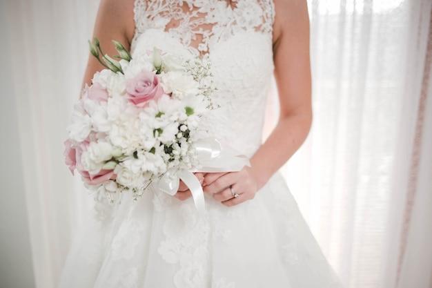 Primo piano di una sposa che tiene in mano un bouquet