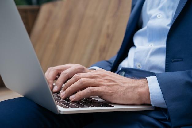 Colpo del primo piano delle mani dell'uomo d'affari usando il computer portatile che digita sulla tastiera che acquista un progetto di lavoro online