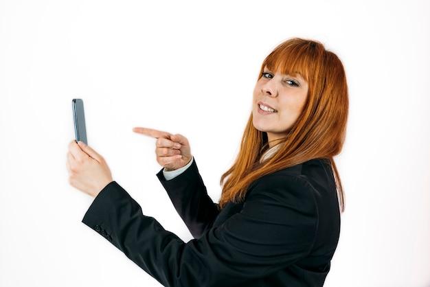 Colpo del primo piano di una donna d'affari che punta al suo telefono su un muro isolato
