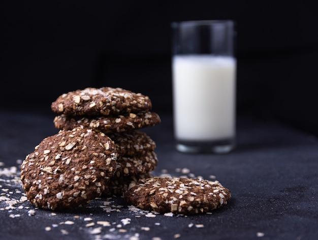 Closeup colpo di biscotti d'avena al cioccolato e un bicchiere di latte su un nero