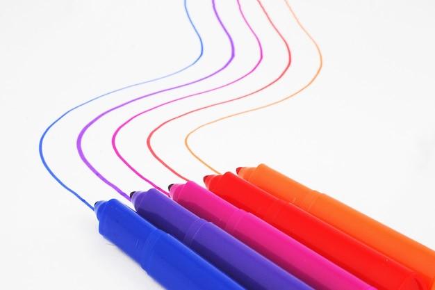 Colpo del primo piano di pennarelli colorati che tracciano linee su una superficie bianca
