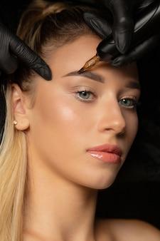 Colpo del primo piano dell'estetista in guanti che fa il trucco permanente della fronte a una giovane donna bionda nel salone di cosmetologia. primo piano