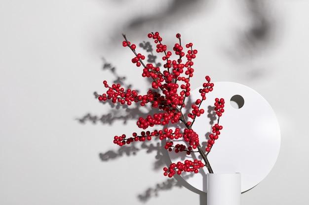 Colpo del primo piano di un vaso decorativo con bacche rosse selvatiche contro un muro bianco
