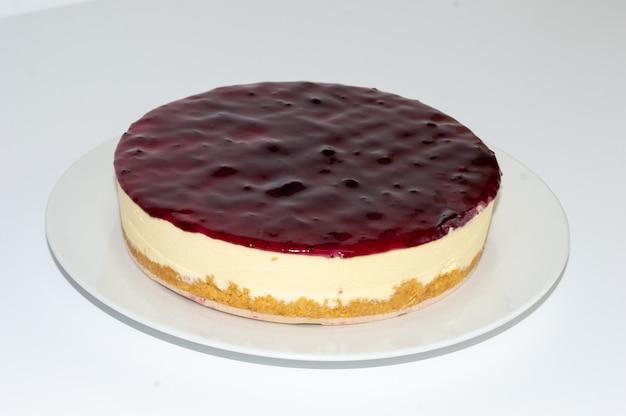 Colpo del primo piano di una deliziosa cheesecake ai mirtilli su un piatto bianco