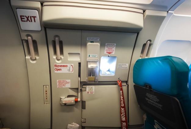 Primo piano della porta dell'uscita di emergenza in aereo