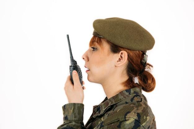 Colpo del primo piano di una donna in servizio militare che dà il comando su un muro isolato