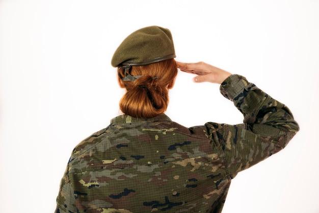 Colpo del primo piano di una donna nel servizio militare su un muro isolato