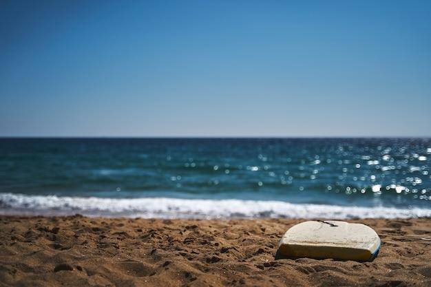Colpo del primo piano delle onde schiumose nella spiaggia zahara de los atunes, cadice, spagna