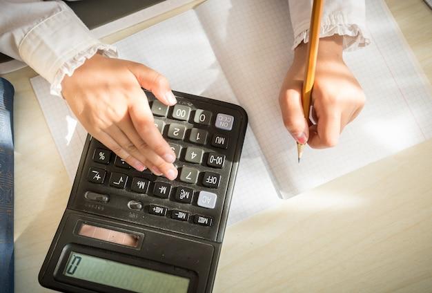Colpo del primo piano della ragazza che risolve il compito di matematica sulla calcolatrice
