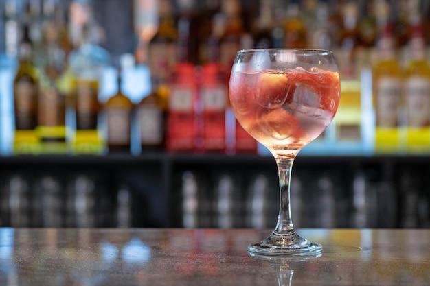 Primo piano di un bicchiere di cocktail rosso ghiacciato sul bancone di un bar