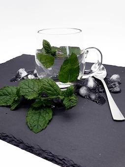 Colpo del primo piano di un bicchiere d'acqua con ghiaccio e foglie di lime fresco