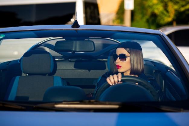 Colpo del primo piano della splendida donna bruna con le labbra rosse che indossano occhiali da sole alla guida di una cabriolet. spazio per il testo