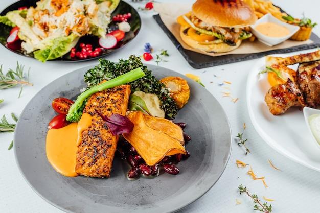 Primo piano di un piatto di pesce gourmet con verdure