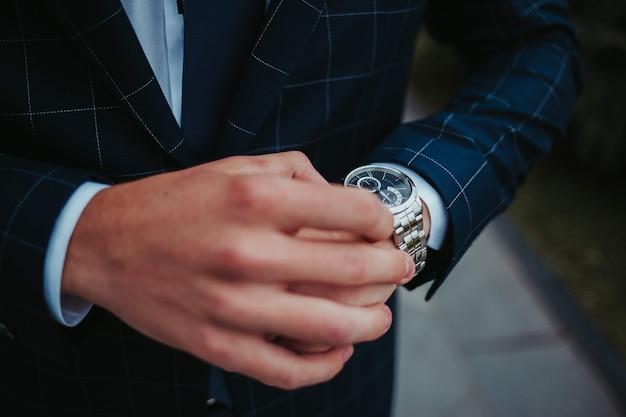 Colpo del primo piano dello sposo guardando il suo orologio