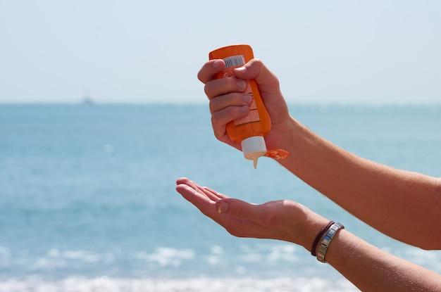 Un primo piano delle mani che mettono la crema solare in una spiaggia