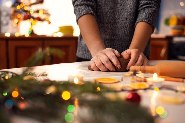 Primo piano delle mani di una giovane ragazza che fa la pasta