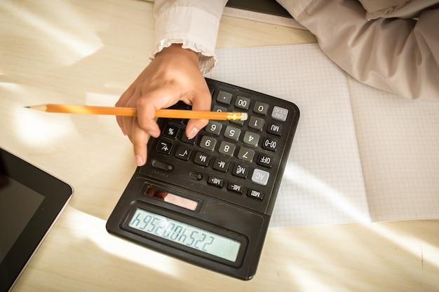 Colpo del primo piano della bambina che tiene la matita e usa la calcolatrice