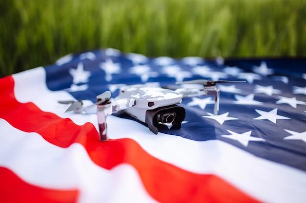 Un primo piano di un drone sdraiato. il drone giace sulla bandiera americana su un campo di grano verde.