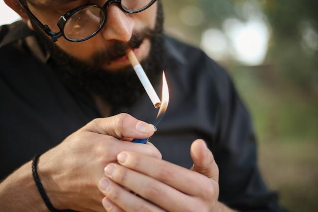 Colpo di primo piano di un maschio accendendo una sigaretta con un accendino