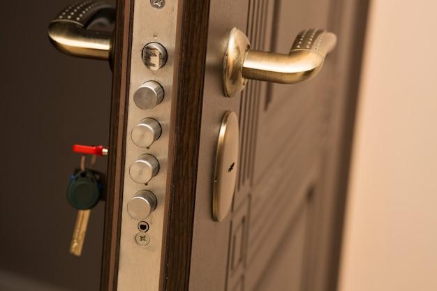 Colpo del primo piano della serratura della porta moderna con una chiave. spazio per il testo