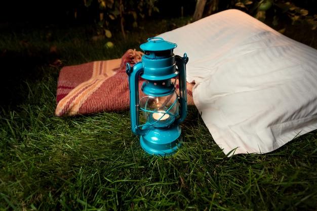 Primo piano di una vecchia lampada a olio in piedi sull'erba accanto al cuscino e alla coperta