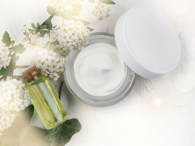 Closeup colpo di olio biologico e crema. disposizione cosmetica verde, cosmetici per la cura della pelle a base di erbe fresche. olio essenziale, bottiglia artigianale, fiori, crema viso vaso.